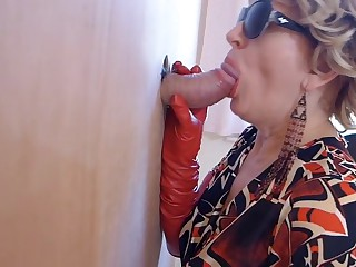 Milf in boots watches porn and enjoys gloryhole blowjob